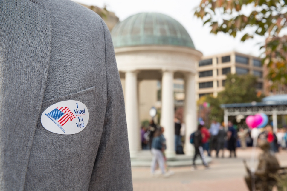 blazer on a person's chest with i voted sticker