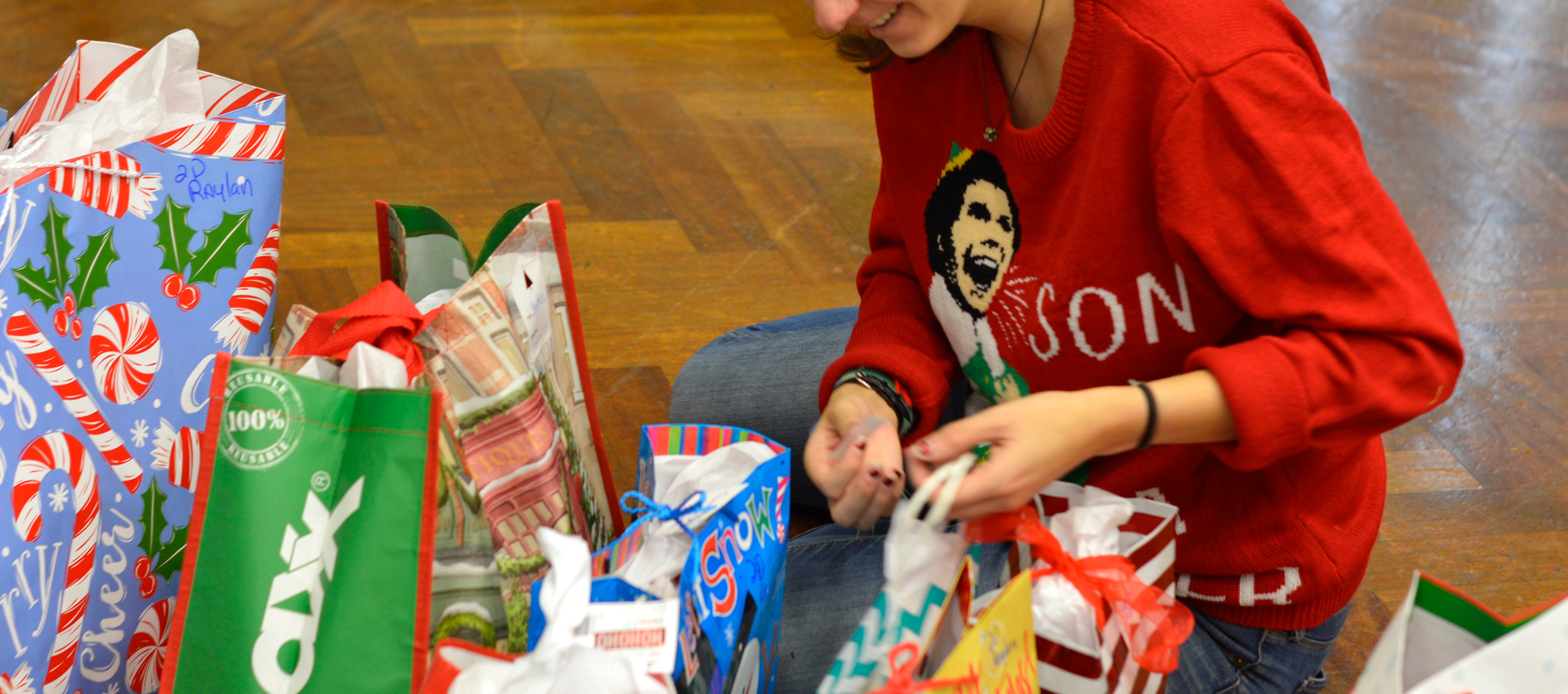 woman wearing a christmas sweater and wrapping a gift