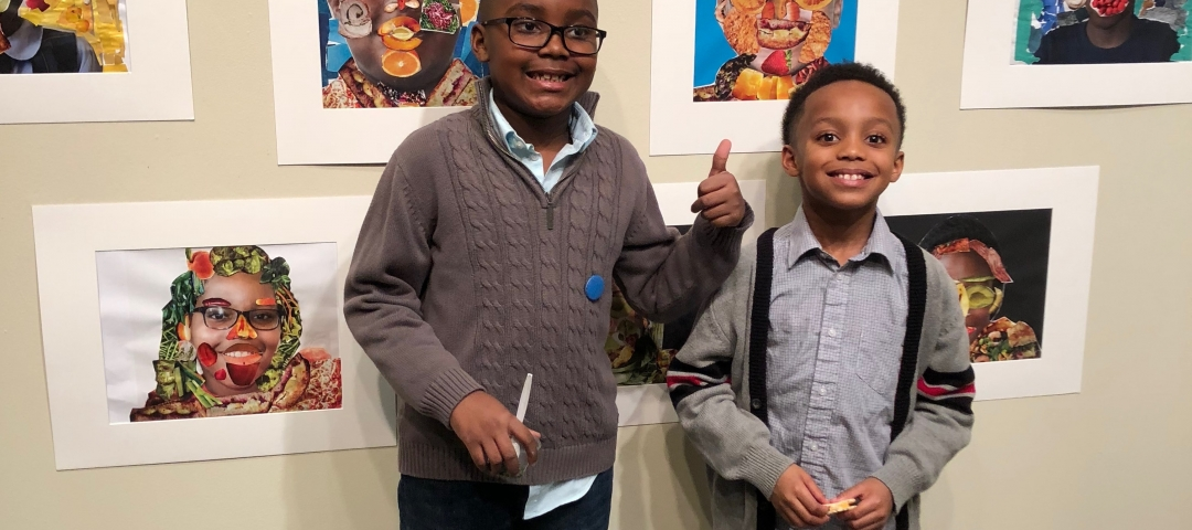 young boys standing next to their work at the ArtReach GW Community Gallery
